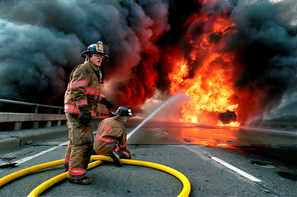 Fireman attack a blazing highway fire. Photo by Rex Larsen.