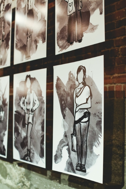 "Illustrations of all 8 stories hung in the background. Featured here is ""Victoria."" (Illustrations by  Michelle Baldwin .)"