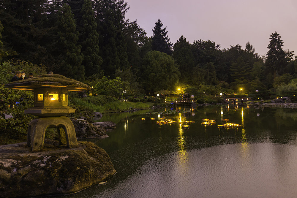 Floating origami boat luminaries placed in the pond by the guests (Photo by SlickPix Photography)