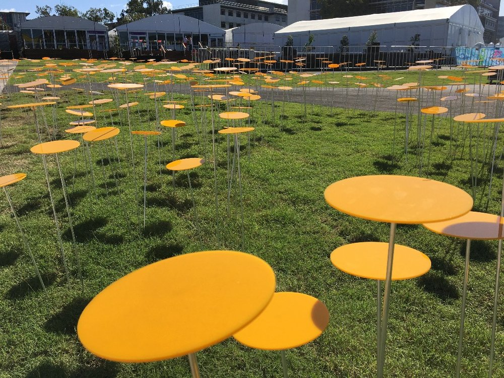 In 2006, Queensland artist Elizabeth Poole exhibited  Blooming Yellow Wave  for SWELL Sculpture Festival. The blooms stood gloriously amongst the Currumbin Beach dune, simulating the way wildflowers grow.  For the Gold Coast 2018 Commonwealth Games, SWELL commissioned Elizabeth to rework the installation on a grand scale with the 853 medal winning athletes at its core as the  Medal Blooms  installation. Each solitary flower stands tall yet unified. Every bloom represents a multitude of stories, growing with the achievements and triumphs of the Games.   As an artist, Elizabeth Poole plays at the intersections of art and nature. The Medal Blooms work responds directly to the surrounding local environment and draws upon the cheerful Climbing Guinea Flower, indigenous to the coastal regions of Eastern Australia.   The climbing flower provides a metaphor for the Athletes competing at the Games, who are undertaking a climb of their own - to reach their personal peak at the top of their chosen field, being recognised by the highest awards of Gold, Silver and Bronze.   The enthusiasm of colour and curvilinear energy rippling from a centre point invites the viewer to immerse themselves in the incredible achievements and feats unfolding during the Gold Coast 2018 Commonwealth Games as each bloom transforms with the medal winners names over the duration of the Games.      VIEW THE MEDAL BLOOMS GALLERY >>>