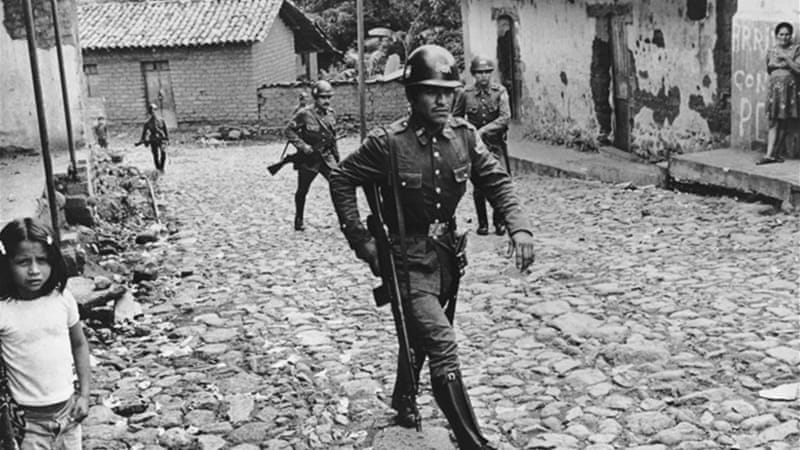 Armed soldeirs walk through a Salvadoran village in the 1980s / Photo  Al Jazeera