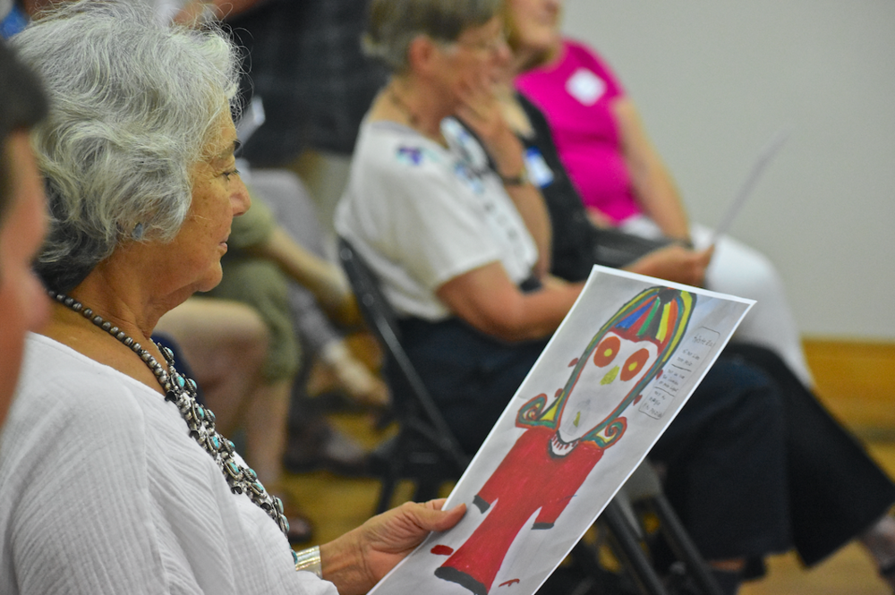 An All Saints' event attendee examines a drawing and poem created by a girl in Cristosal's protection program
