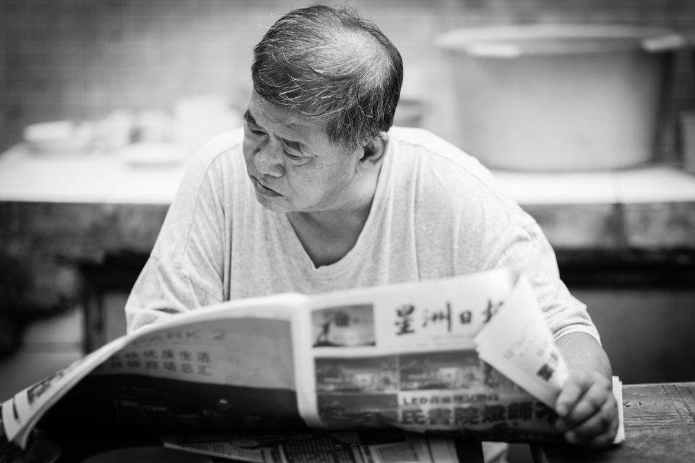 pasar-karat-man-reading-newspaper-kuala-lumpur.jpg