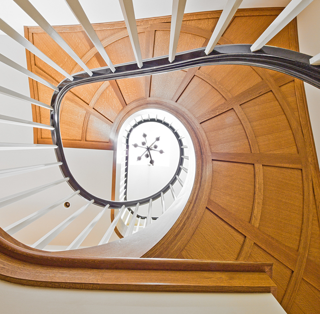 An uplifting view of the West Seattle staircase highlighting a complex ceiling detail / Seattle Stair & Design