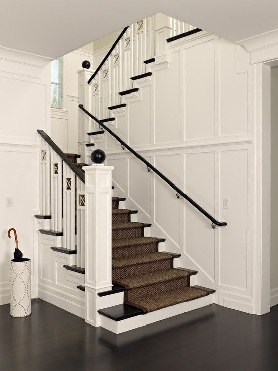 A dark stained rail has been mounted at the wall, matching the style of the rest of the staircase. Polsky Perlstein Architects | Photo by Mark Schwartz Photography