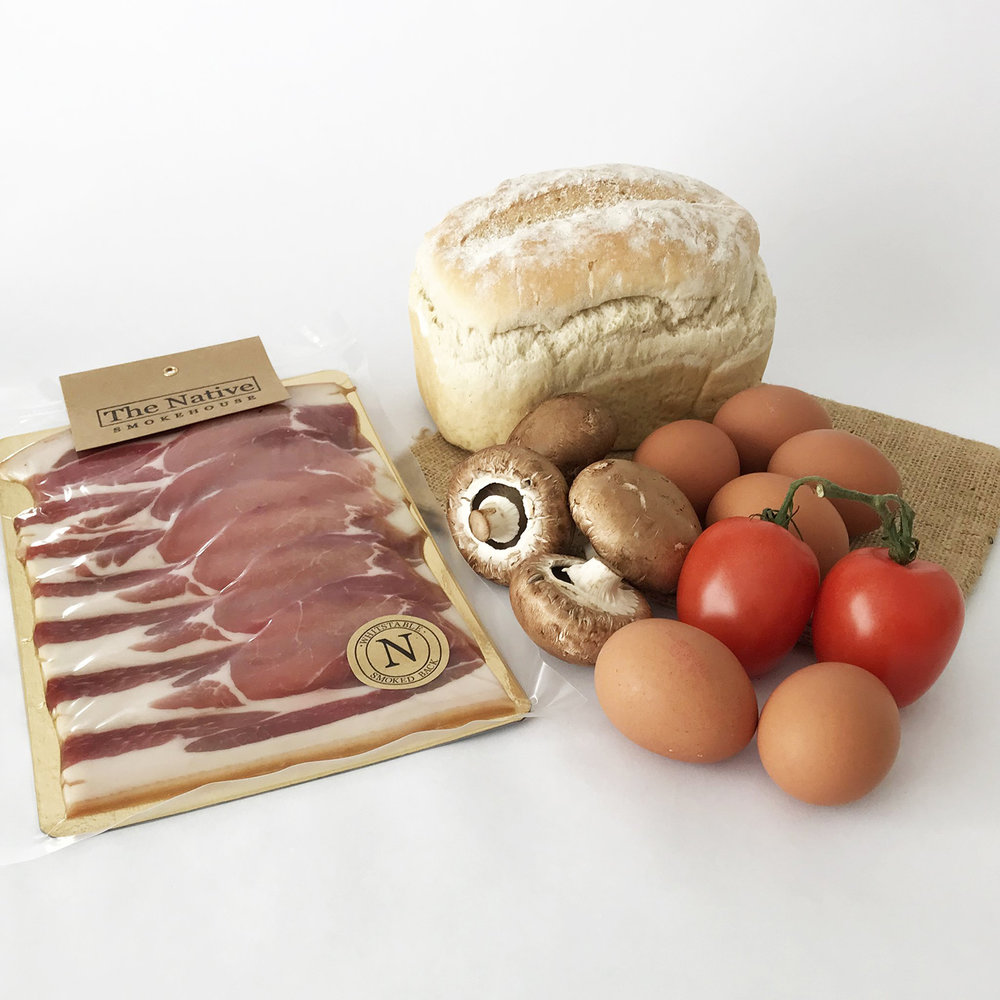 Whitstable Best Breakfast - This breakfast box is £15 - will be enough for up to three peopleThis item needs one week notice please.Enjoy your own view and a leisurely start to the day over a traditional English breakfast food box supplied to you by Whitstable Larder and sourced locally from Whitstable High Street. Smoked bacon is the true star of this breakfast box, all prepared just a pebble's throw away from the High Street. Perfect for a Kent Breakfast Taste of Whitstable Weekend - local delivery only.For something extra special, enjoy oak smoked Back Bacon cured and smoked in Whitstable by epicurean Chris of The Native Smokehouse. The Smokehouse Bacon is made using only outdoor reared and free range English Pork which is then dry cured and air dried before slowly smoking over oak as part of the traditional preserving method to give an 'old fashioned bacon, dry to the touch and robust in flavour, just like bacon used to be'.We pair the bacon with local free-range eggs from Woodland Farm in Kent which we buy from Jim's Butchers, bread baked in Hubbard's Bakery Whitstable and tomatoes and mushrooms from Whitstable Green Grocer Staines Farm Shop.Contents- Whitstable Native Dry Cured Smoked Back Bacon 220g- Woodlands Farm Free range Eggs Laid in Kent (half a dozen large eggs)- Chestnut Mushrooms 100g- Vine Tomatoes 150g- White Loaf from Hubbard's Bakery - SmallFind out more →