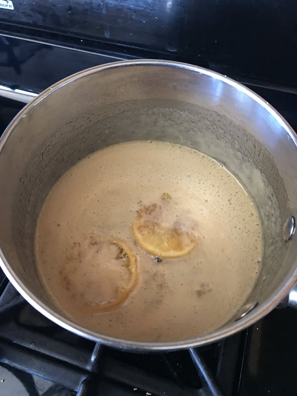 Here is the honey, some lemon slices, and the lemon zest simmering slowly.