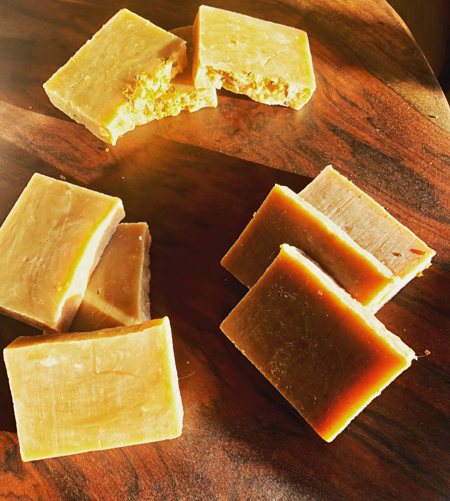 Here are three different milk soaps made using the hot process method. The one on top is coconut milk soap. I did color it with a little turmeric, or it would have been a bit lighter. The one on bottom right is a buttermilk and honey soap. Honey tends to darken soaps a bit, too. The one on the left is a buttermilk, honey, and vanilla oatmeal soap. It's quite a bit darker, and this is due to the vanilla extract.