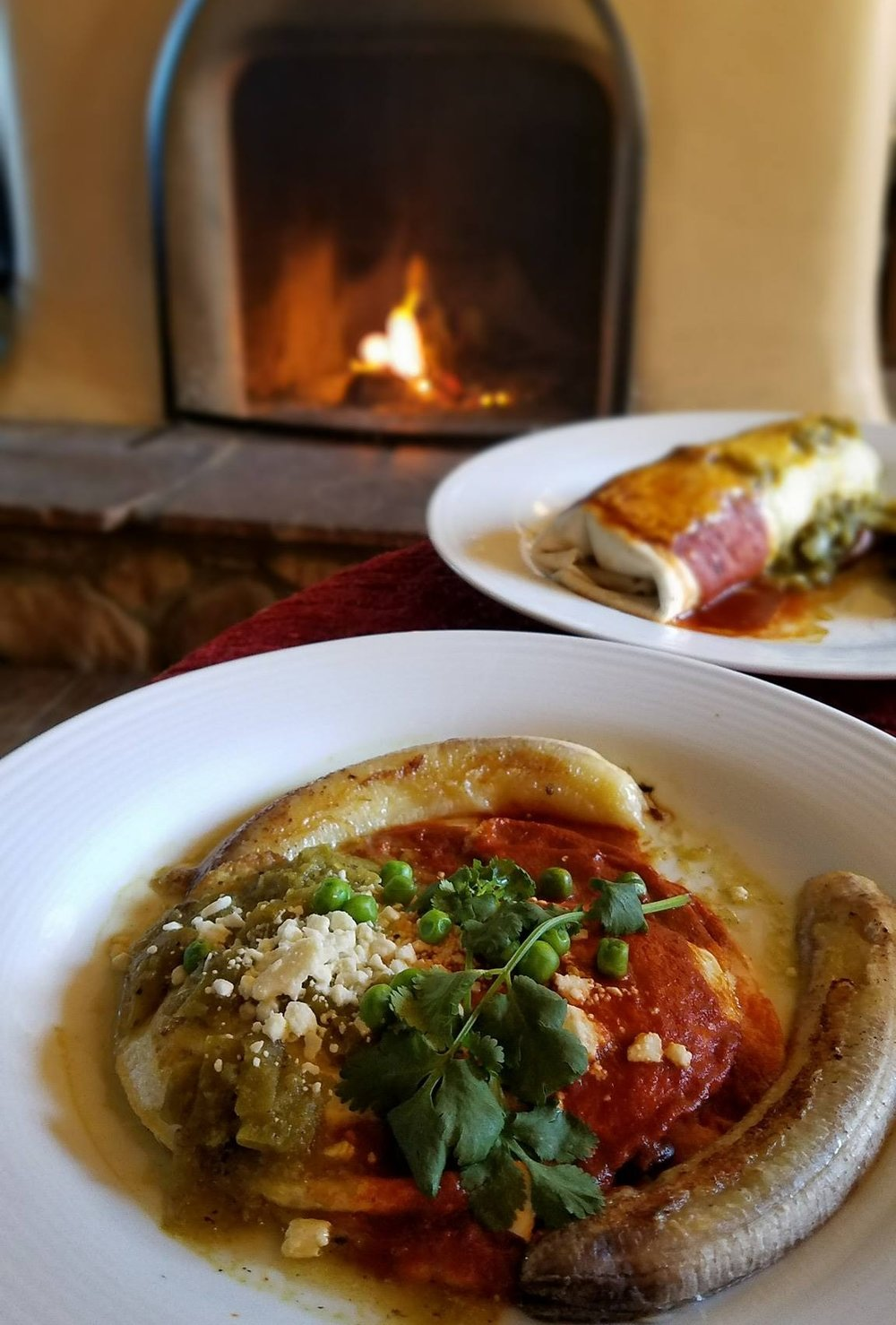 Huevos Motulenos - Eggs over easy atop beans and white corn tortilla, topped with Rosa's salsa, peas, feta cheese, fried banana topped with red and green chile.
