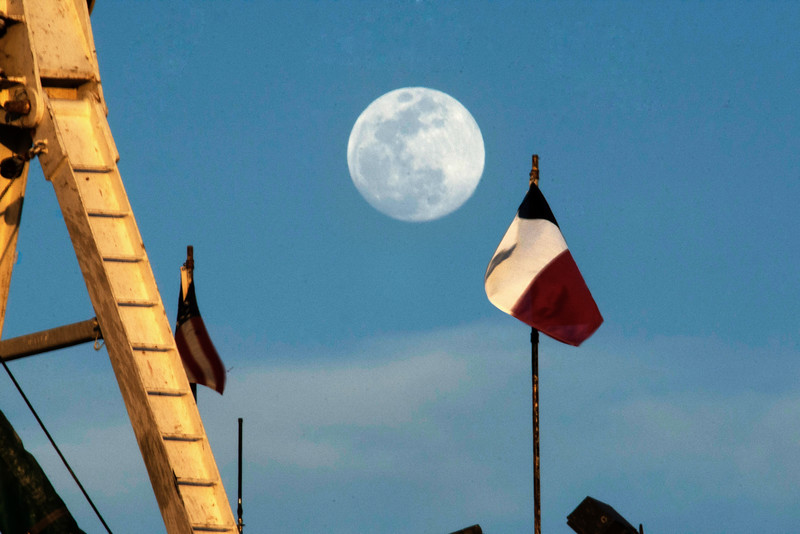 Flags on flagspole moving with the wind down sky with the moon over