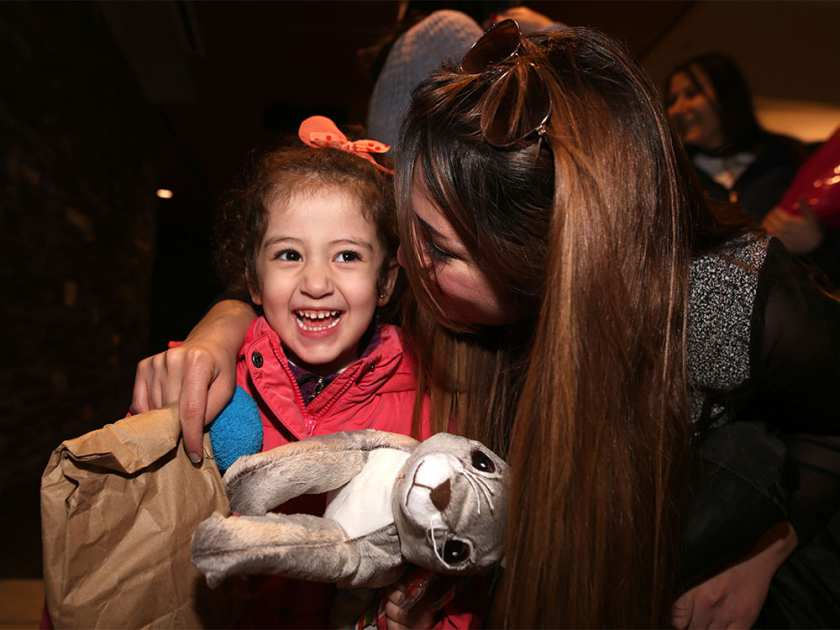 refugee child appreciates a stuffed animal and hug