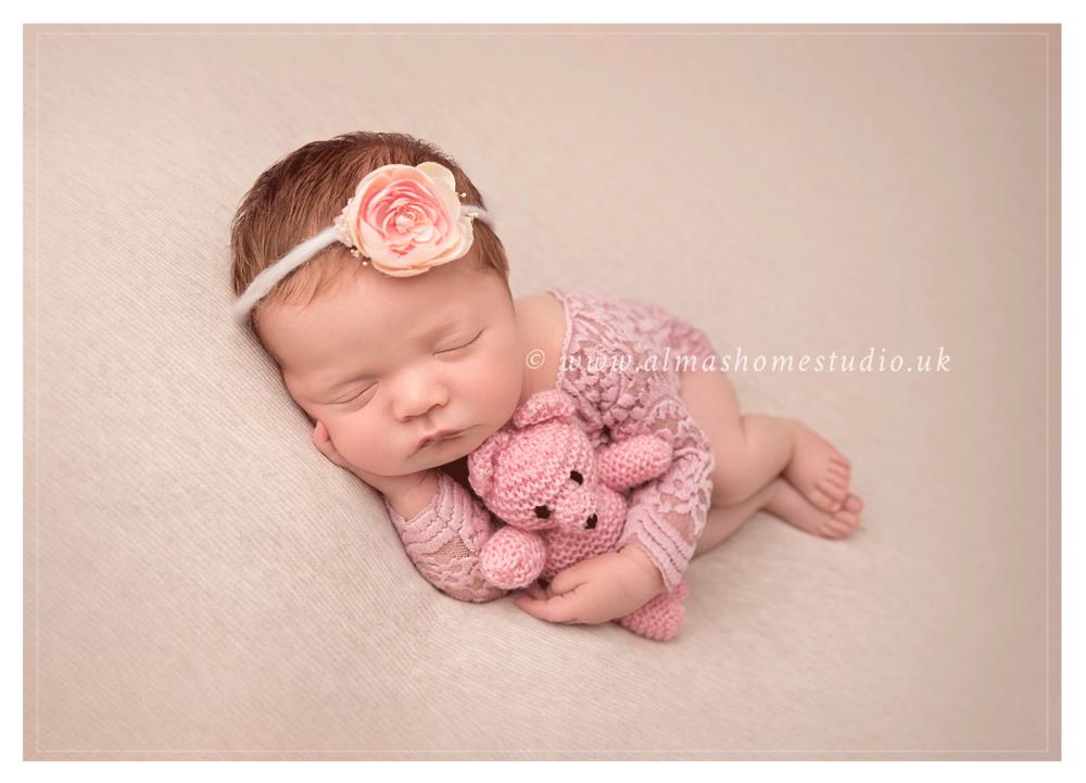Newborn girl cuddling teddy