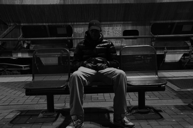 dark image of man sitting on a bench