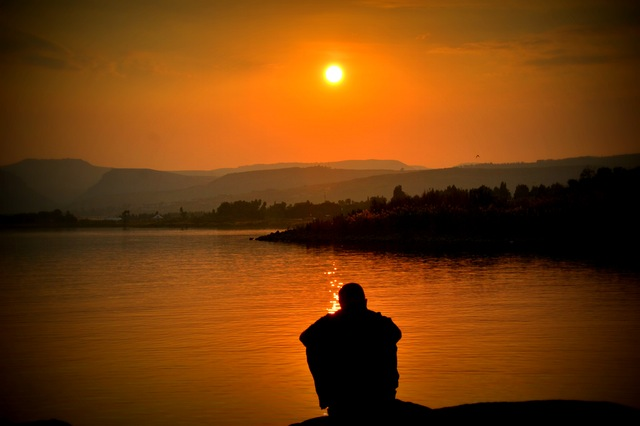 man sitting overlooking mountain lake sunset