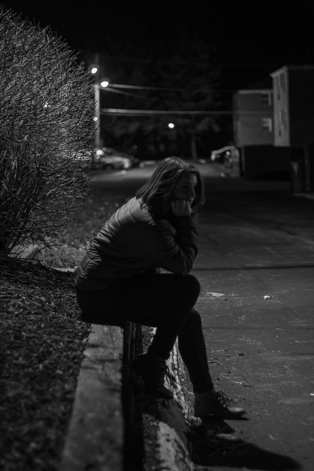 woman sitting in the dark outdoors