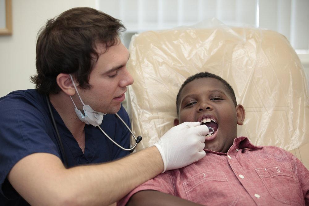Dentist cleaning kids teeth