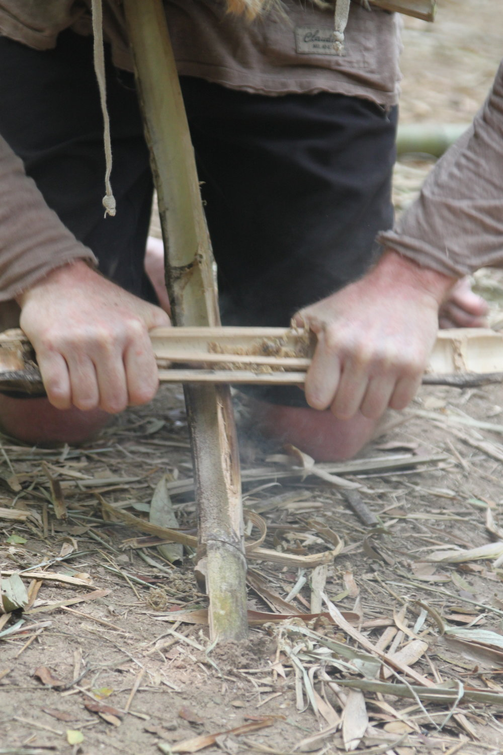 Mastering fire with a bamboo fire saw.