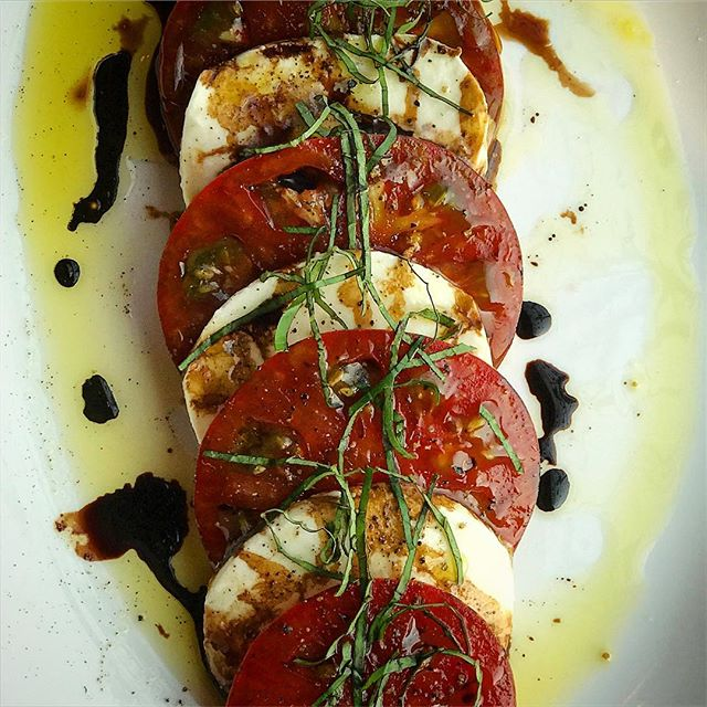 We have two words for you: Caprese. Salad.  Heirloom tomato, mozzarella, basil, olive oil, balsamic reduction. #capresesalad #localproduce #yum