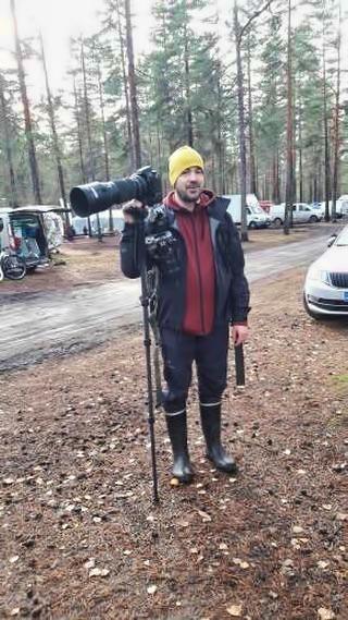 Rähjäinen ja väsynyt mies. Käsissä kombo jonka kanssa oli jo pakko ottaa avuksi hiilikuituinen monopodi. Jytky (kamera+putki+akkukahva+2kpl akkuja) on painoltaan varmaan yli 4.5kg. Kädet väsyy liikaa ja kuvaus kärsii ilman apuja. Toinen kamera roikkuu repun olkahihnassa.  Kuva: Anna/ Trailwind Huskies