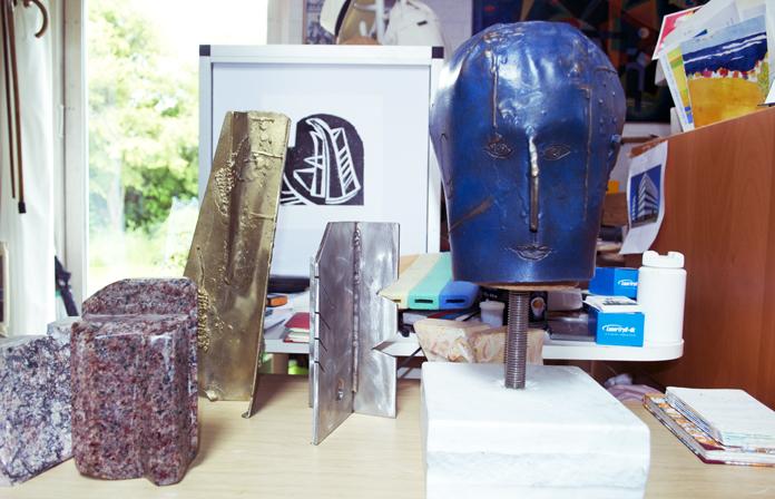 Josephs selvportræt i patineret bronze og nogle mindre skulpturer i metal og sten. I baggrunden et linoleumstryk.