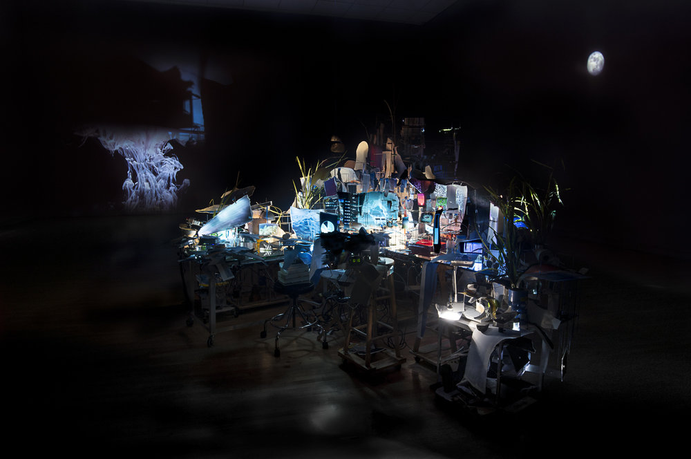 Sarah Sze, Timekeeper (2016), Mixed media, mirrors, wood, stainless steel, archival pigment prints, projectors, lamps, desks, stools, stone. Dimensions variable. Courtesy of the artist, Tanya Bonakdar Gallery and Victoria Miro Gallery. © Sarah Sze.
