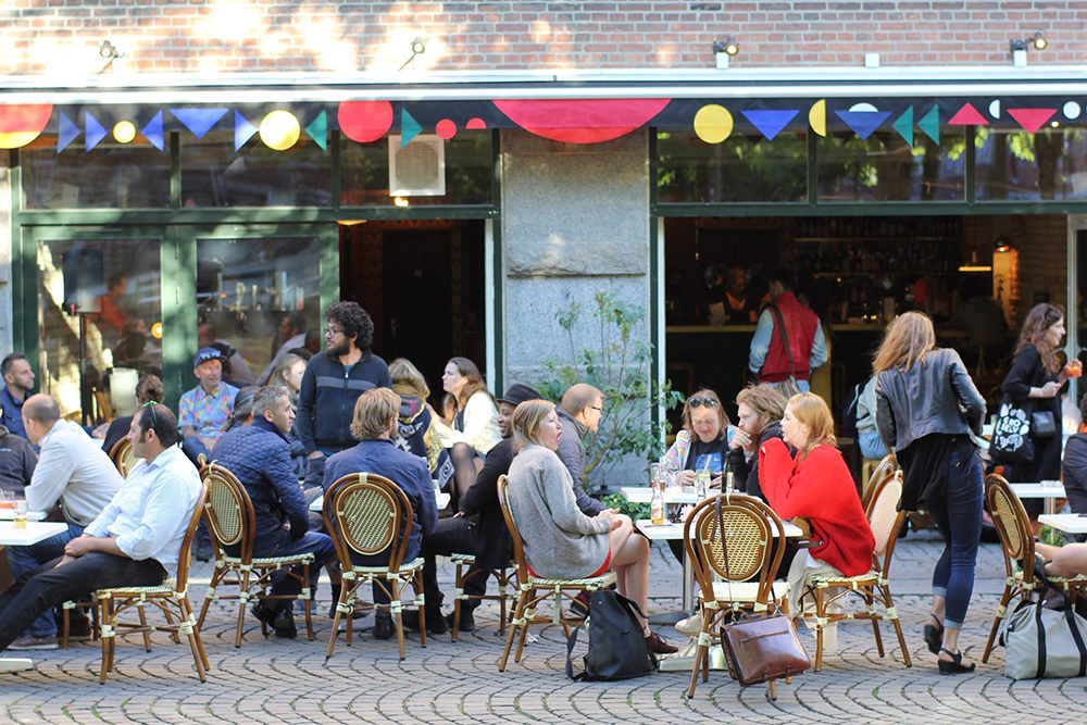 "Sorte Firkant   ""Sorte Firkant is a bar & cultural venue located in Blågårdsplads Copenhagen. The aim of Sorte Firkant is to create ""plads"" - or space for artists and cultural workers whose work occupy a non-identitarian identity. Which is to say that the work is not easy to situate within the current normative constrains. Sorte Firkant works on the history and density of ""Sorte Firkant"" (The Black Square - the historical name for the area in Nørrebro, where the venue is located), while at the same time, the aim is to deterritorialise the square from its historical and cultural connotations, to create a social space where artists from various different backgrounds can come together across art forms and develop their work collectively. The aim is to create a community of sharing of work and experiences; a platform where to discuss your work with friends and colleagues in an intimate setting and to take that work further to the public. In the fall of 2017 we are launching Sorte Firkant's new project space in the basement under the café.""   Addresse:  Blågårdsgade 29AE, 2200 København N.  Links:   Facebook   Foto:  Frank Piasecki Poulsen, 2016."