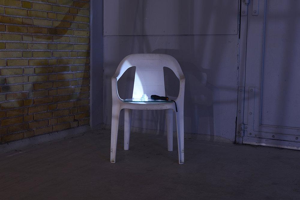 Kontakt, 2018. Plastik-havestol, glasplade à 25x25cm, lommelygte og brugte kontaktlinser. (Belysning af indtørrede kontaktlinser indsamlet gennem en årrække). Foto: Heidi Hove.