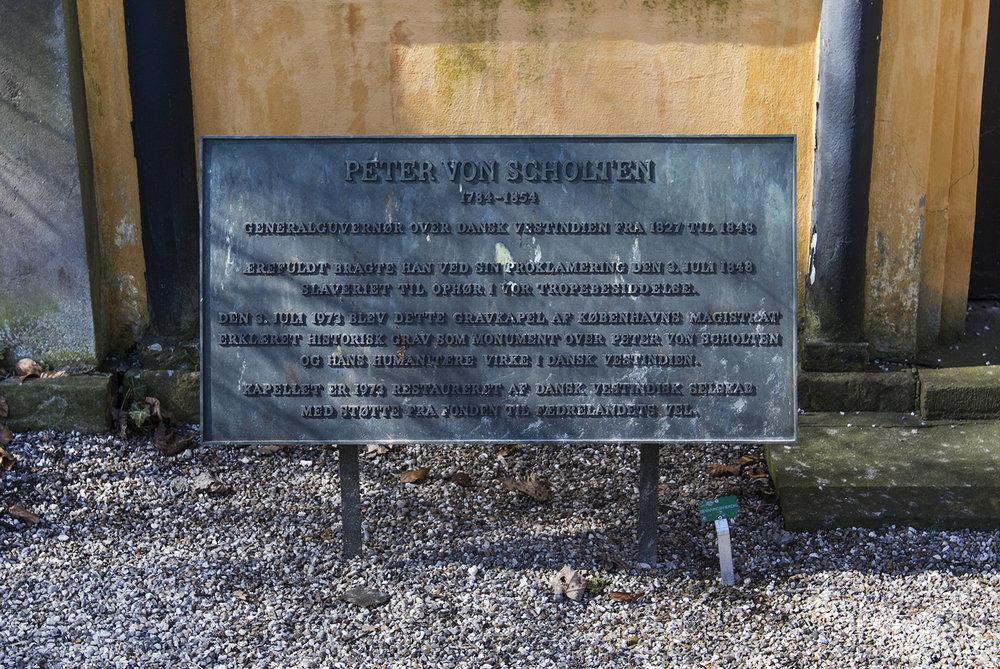 """""""Peter von Scholten, 1784 - 1854. Generalguvernør over Dansk vestindien fra 1827 til 1848. Ærefuldt bragte han ved sin proklamering den 3. juli 1848 slaveriet til ophør i vor tropebesiddelse. Den 3. juli 1973 blev dette gravkapel af Københavns Magistrat erklæret historisk grav som monument over Peter von Scholten og hans humanitære virke i Dansk Vestindien. Kapellet er 1973 restaureret af Dansk Vestindisk Selskab med støtte fra fonden til fædrelandets vel.""""  står der på mindetavlen foran von Scholtens mausoleum på Assistens Kirkegåden. I Danmark er von Scholten blevet hyldet som helt, men på Jomfruøerne er historien en anden. Photo © I DO ART Agency."""