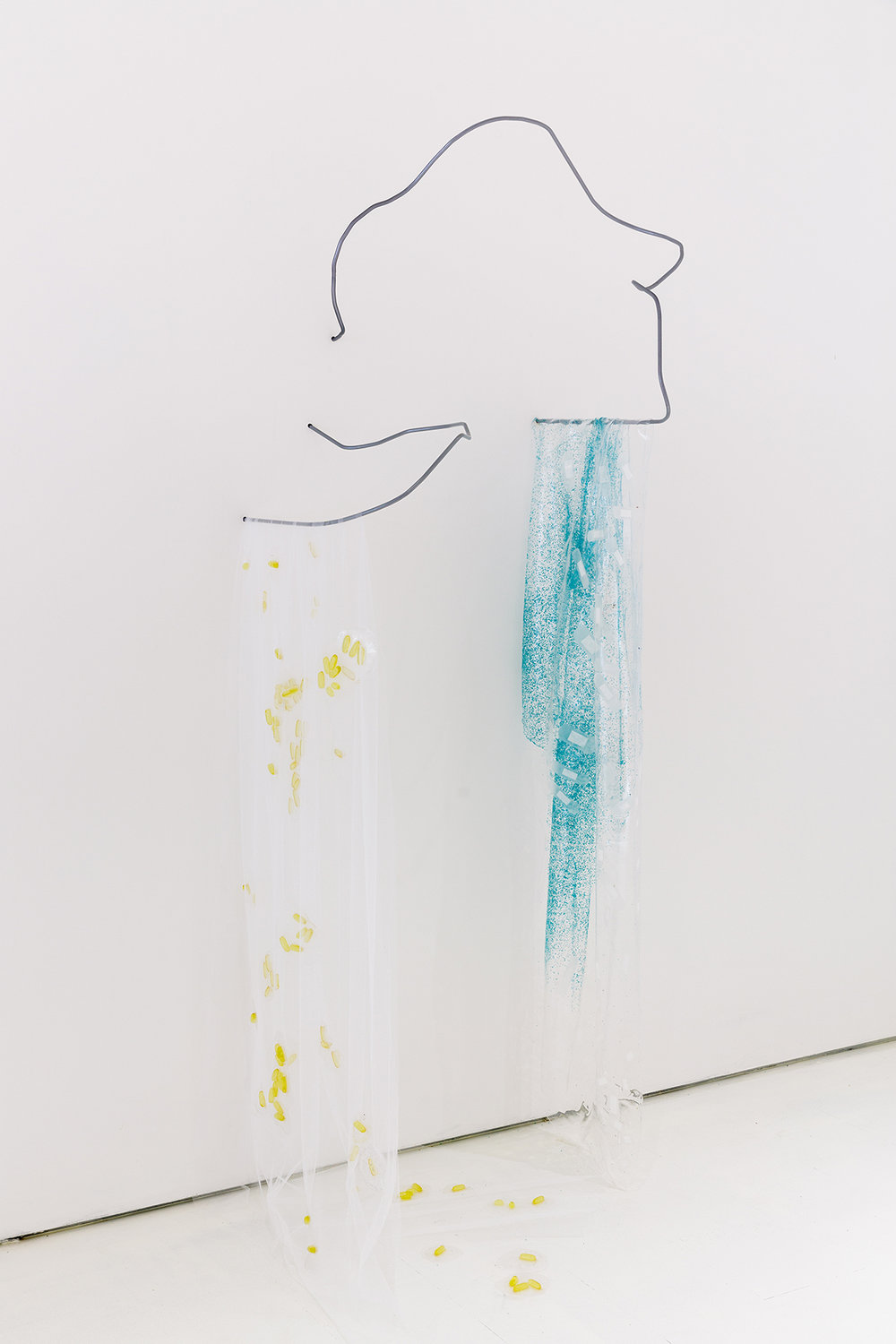 Leah Carless. Soft Cover (glowing) (Powder coated steel, polyester mesh, silicone, fish oil capsules, evening primrose oil capsules 60 x 130 x 60 cm). | Leah Carless. Soft Cover (itchy) (Powder coated steel, silicone, polythene micro beads, plasters 40 x 175 x 45 cm). Photo: Tim Bowditch.