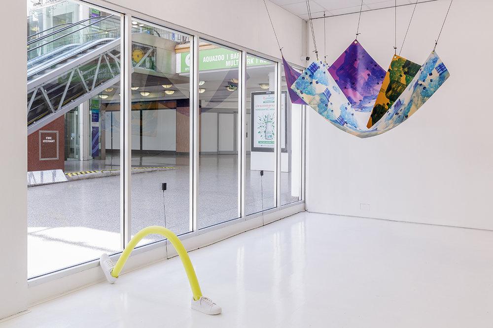 Mette Boel. Hammocks for the Future. 2018 (Digital print on tarp, eye lets, para cord, trockles. 200 cm x 100 cm x 120 cm). Mette Boel. Limbos II. 2018 (Heat treated swim noodle, rubber shoes. 120 cm x 60 cm). Photo: Tim Bowditch.