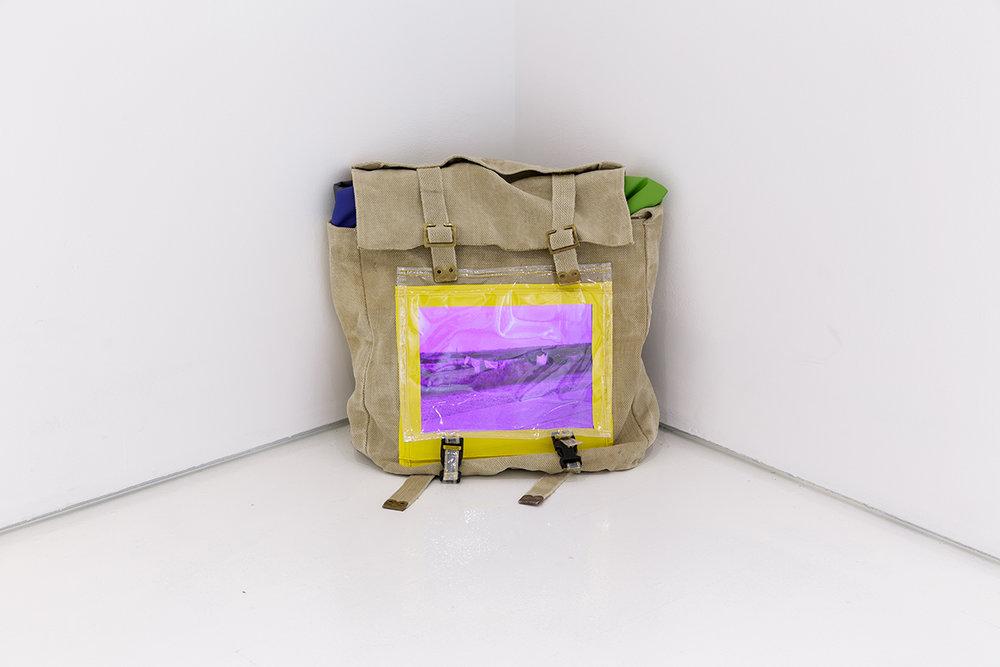 Mette Boel. Bug Out Bag 2018 (Screen w. 41 digital images, army bag, rain proff fabric, plastic, clasps. 30x35x20cm). Photo: Tim Bowditch.