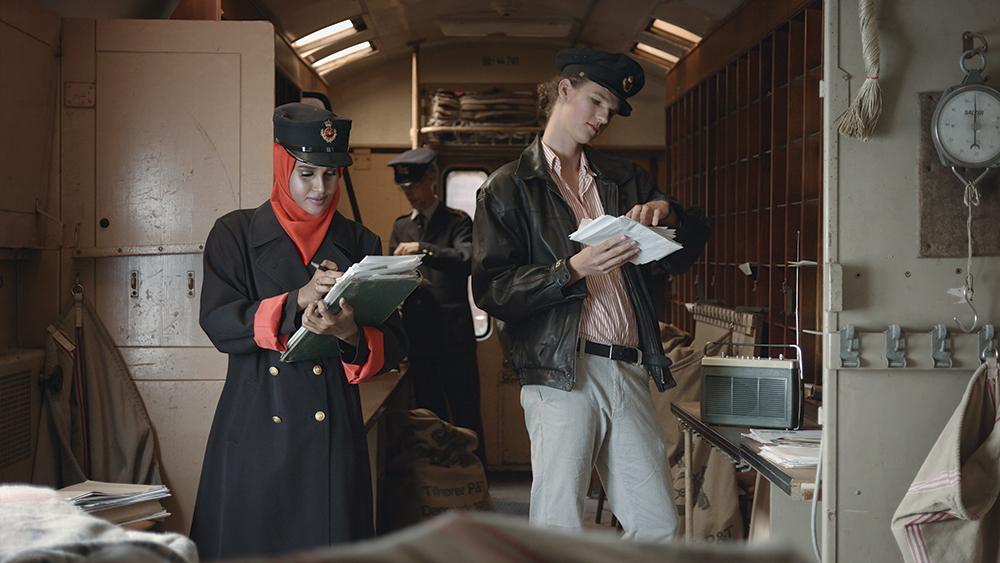 Performerne Sagal Ibrahim Abdiwali, Kaj Rasmussen, Jonatan Rønsholdt i en postsorteringsvogn på Midt- og Vestjyllands Jernbanemuseum / Struer Museum. Foto: Mads Hoppe.