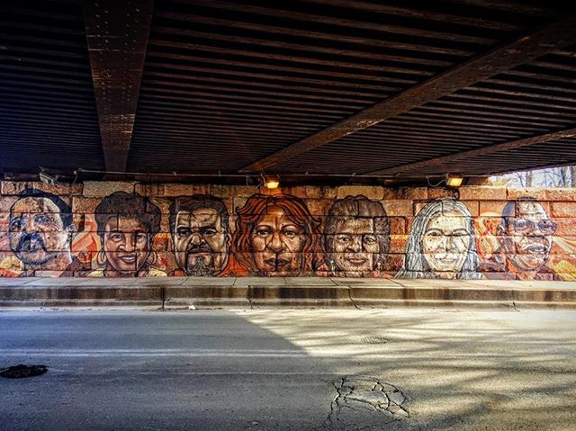 """Sepia""  2016  La Villita. 23rd and Central Park.  Lead artists: Rahmaan Statik Max Sansing  The first mural of it's kind. The artists use sepia tones, the color tones of people, to camouflage the rust that will eventually drip down from the railroad bridge. The people depicted are all members of the community.  Sponsors:  Chicago Public Art Group 22nd Ward Alderman Office"