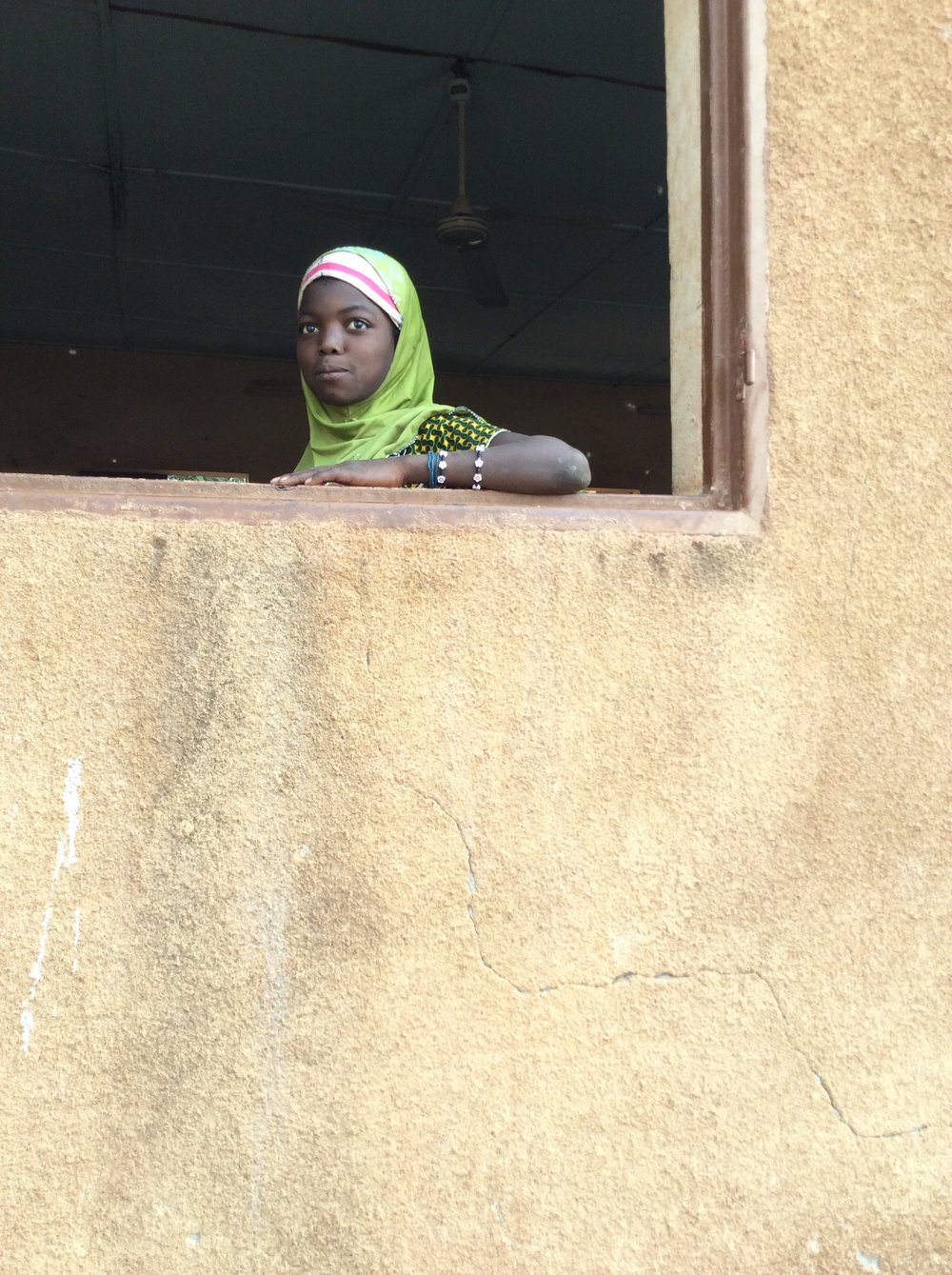 A young girl looks out the school window in our partner village, Beneko.