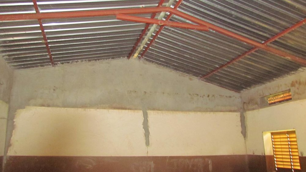Inside a classroom, the walls are re-plastered after removal of the ceiling.