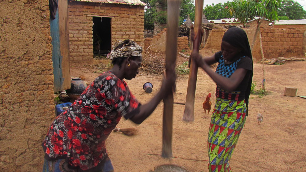 Adiaratou pounding millet with her mother.