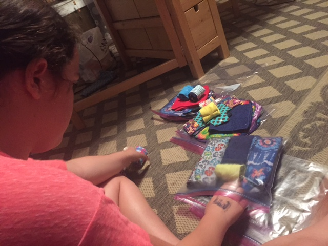 Skyler stuffing the final kits with shields, pads, underwear, washcloths, and more.