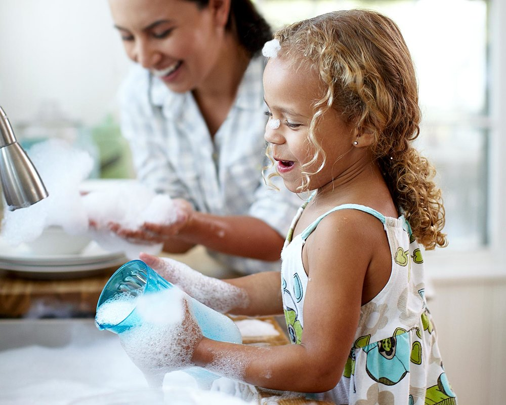 Mother and daughter having fun washing dishes with Legacy dish soap.