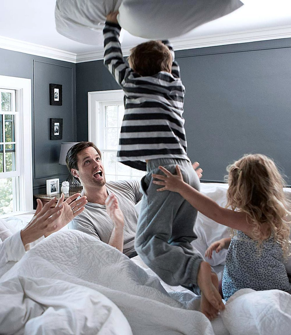 Family time with kids jumping on clean sheets.