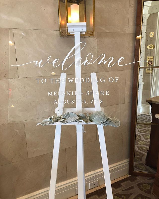 "Welcome to the Wedding of Melanie + Shane... Please find your seat! Custom 24"" x 36"" clear acrylic Welcome Sign and Seating Chart in white ink! 😍😍😍 Stationery: @invitationarchitects Planner: @agriffinevents Venue: @hayadamshotel Florals: @edgefloraleventdesigners Photography: @iamthesam"