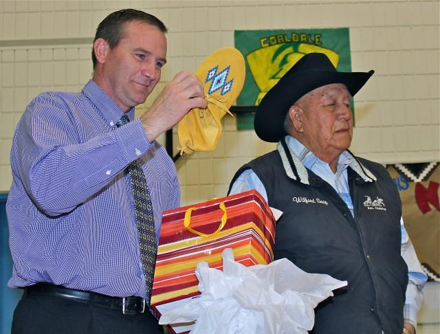 2015 Excellence in Teaching Semi-Finalist, Principal Austin Nunn, holding moccasins presented at an event at Cardston Junior High School with a member of the Blood Tribe.