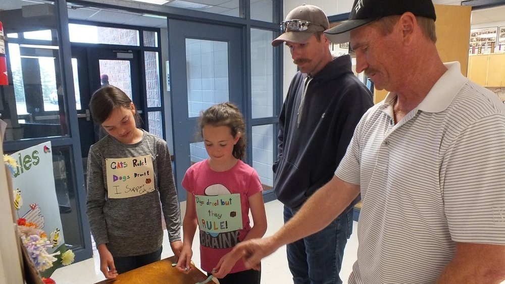 Kate Leishman and Carly Bevans giving hints to Mr. Webster & Mr. Blackmore to help them solve a math story