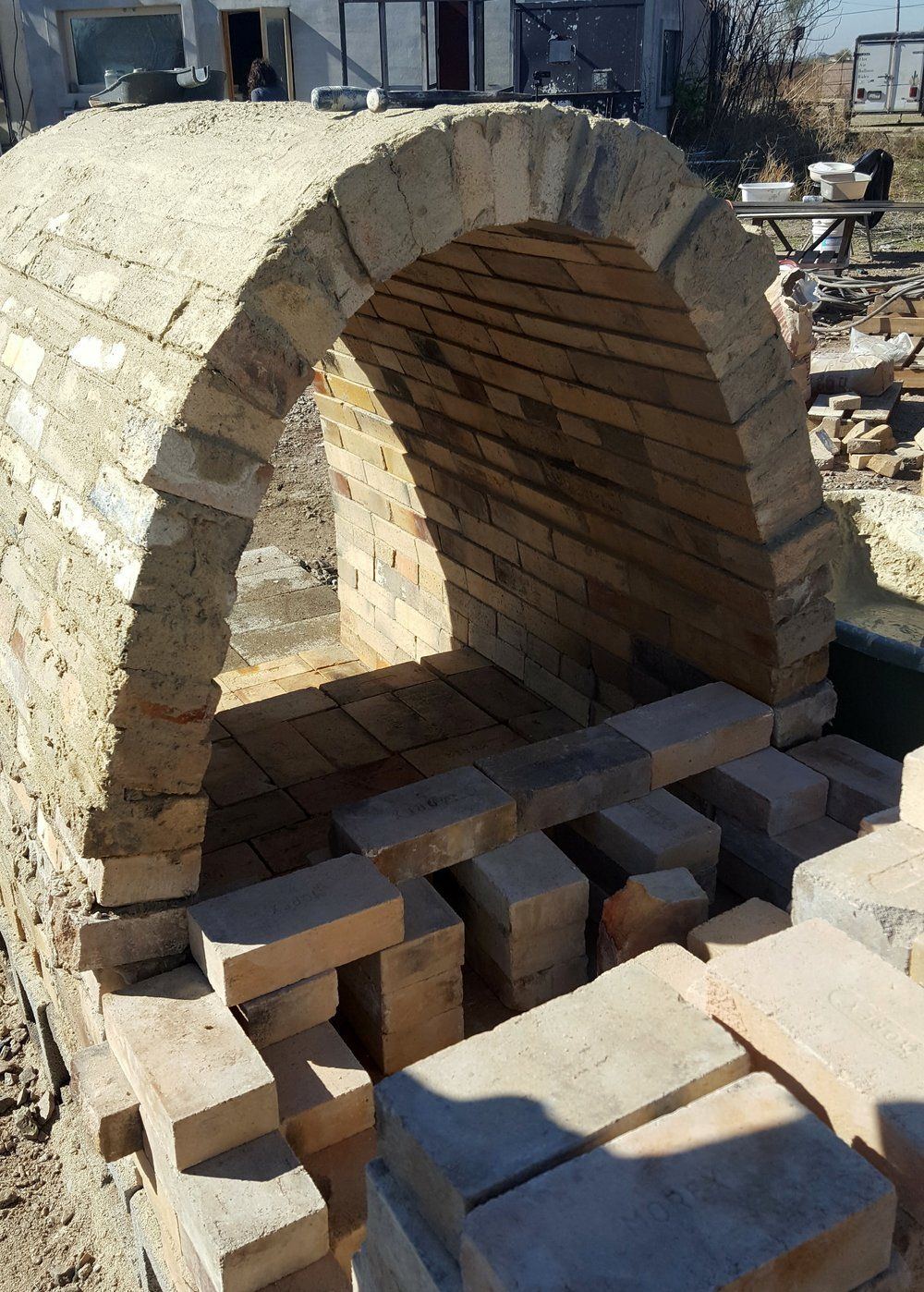 The completed arch from the back, and starting on the chimney.  The chimney, along with little slots at the back of the arch, will help to suck through the air from the front of the kiln out the back.  The arched shape will help the heat and flames circulate evenly through the kiln.