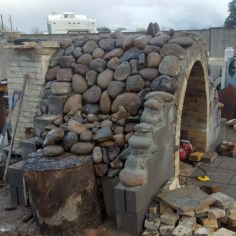 Not only do the rocks look cool, they help stabilize and insulate the kiln,  We used simple cement blocks, and a couple really nice stumps that were hanging out on the Dragons property, to help keep the rocks corralled into place..