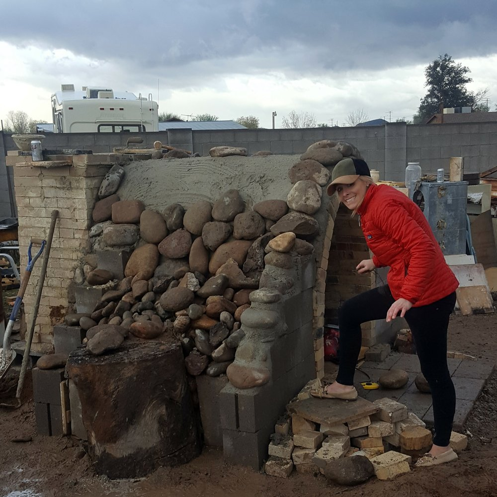 Tracy signing the kiln :)  We covered the kiln arch with castable, and while it was still wet we placed all these large river rocks over it.