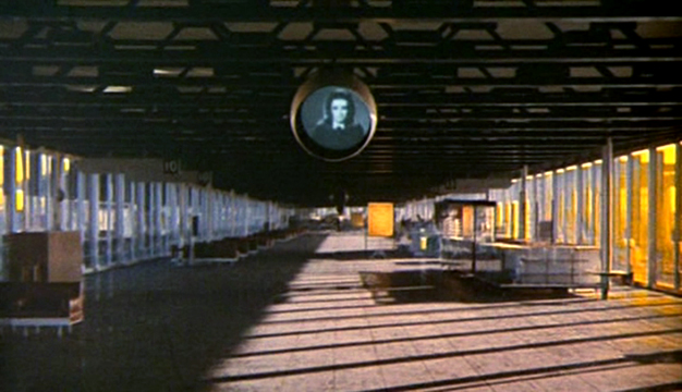 "Toby Dammit  The strangely depopulated airport is both hyper-real and fake, ominous and banal. We might assume it is a painting but for the fact that the camera tracks forward into the space, eventually tilting upwards towards the black and white video screen - an image that seems to come from some other time-frame or reality. The sort of space that would later be referred to as a ""non-place"" by sociologists like Marc Augé."