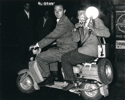 Unknown Photographer,  Tazzio Secchiaroli.  Secchiaroli is at the throttle of a Lambretta with Luciano Mellace behind him with a Rolleicord camera with flash. 1952