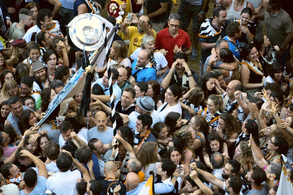 I love this photo.  The emotion in these peoples faces tell the story as they carry off the Palio.