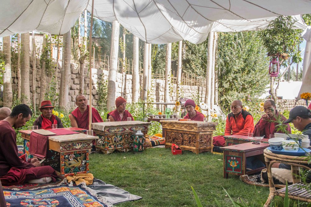 Leh, Pankaj Singh. Monks conducting a holy recital take a break at a home. Traditional tables called the Choktse are laid out to serve them butter tea, biscuits and Thukpa.