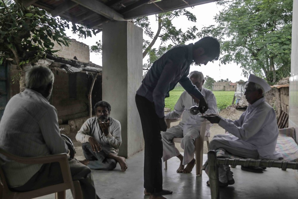 Kesod,  Pankaj Singh . Neighbours rush to Thakar C. Bhai's home to hear his predictions for rain this year. He is the 'Drought man,' a traditional forecaster known to accurately predict rainfall and harvest. Divesh, the grandson pours tea into saucers as the men listen intently.